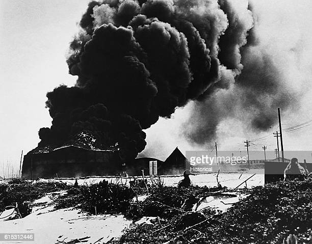 Burning oil tanks hit by Japanese bombs on Midway Island before the Japanese were repelled June 46 1942 Gooney birds in the foreground | Location...