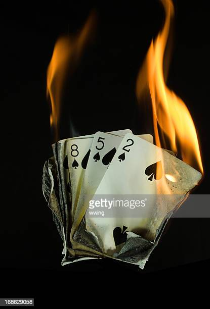 burning poker hand - hand of cards stock photos and pictures