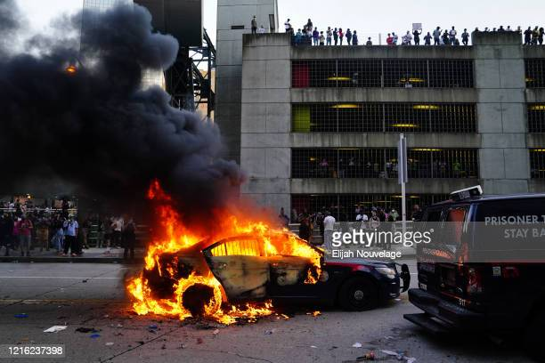 A burning police car is seen during a protest on May 29 2020 in Atlanta Georgia Demonstrations are being held across the US after George Floyd died...