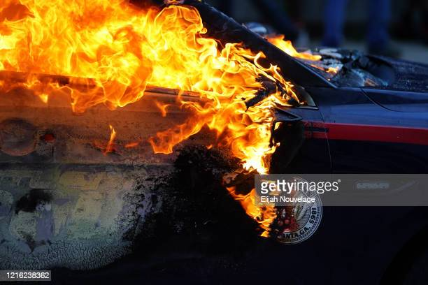 A burning police car is seen during a protest over the Minneapolis death of George Floyd while in police custody on May 29 2020 in Atlanta Georgia...