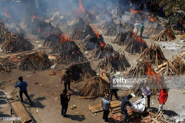Burning pyres of Covid-19 deceased people at a crematorium in New Delhi. India Health Ministry recorded a total of 17 millions infections 192,000...