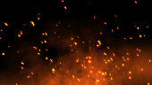 Burning red hot sparks fly away from large fire in the night sky