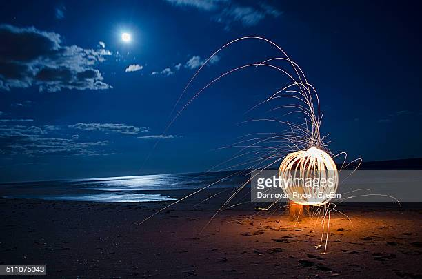 Burning steel wool firework on beach at night