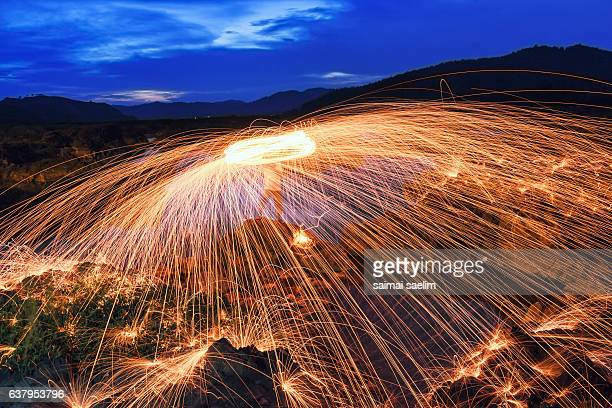 Burning steel wool fireworks during blue hour, Thailand