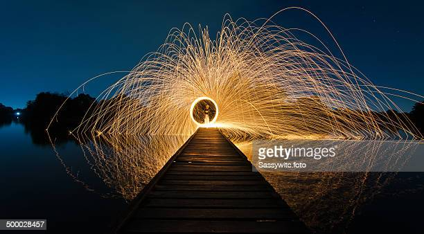 Burning steel wool fireworks on wooden bridge.