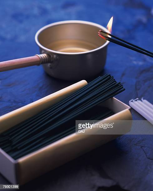 burning sticks of incense, ladle, candles and incense sticks in box, high angle view, differential focus - bon fire stock photos and pictures