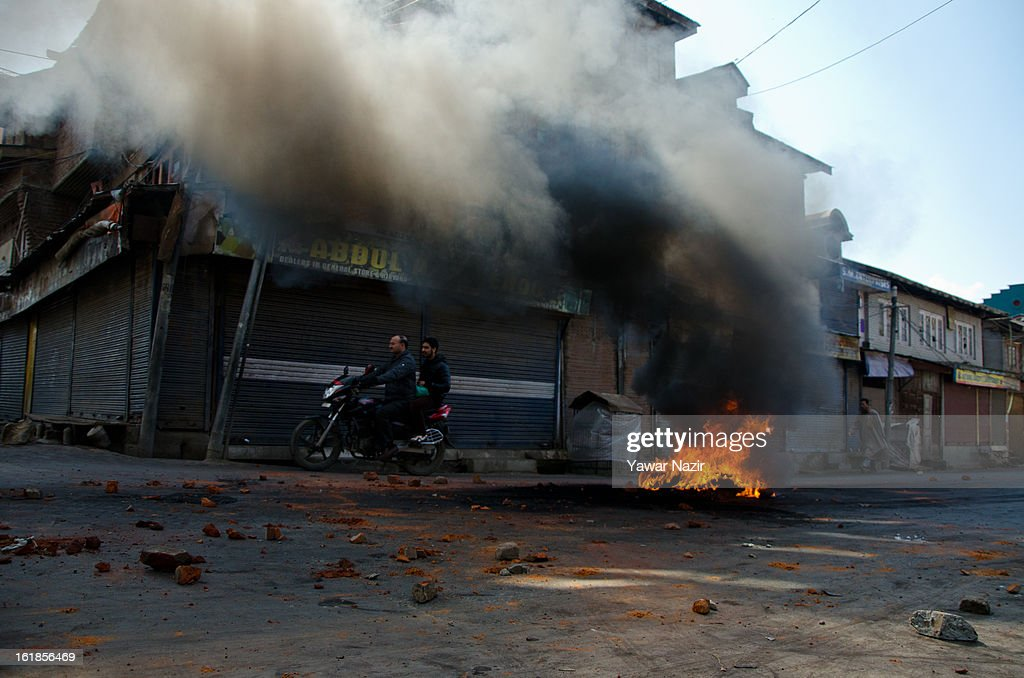 Burning tires are left in the middle of a road during a strike call given by separatists against the execution of alleged Indian parliament attacker Mohammad Afzal Guru on February 17, 2013 in Srinagar, the summer capital of Indian Administered Kashmir, India. Normal life remains affected in Indian-administered Kashmir for the ninth consecutive day as a complete shutdown was observed on the call of separatist leader Syed Ali Shah Geelani. Afzal Guru was hanged on February 9 for his alleged role in the 2001 Indian parliament attack which left 14 dead. Clashes between Kashmiri youth and Indian police were also reported in several parts of the disputed Himalayan region, which was put under a strict curfew for a week by Indian authorities worried about massive public protests following Guru's hanging last Saturday.