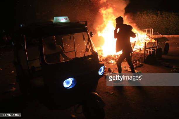 Burning tyres light up the night skies during anti-government protests in the Shiite shrine city of Karbala, south of Iraq's capital Baghdad, late on...