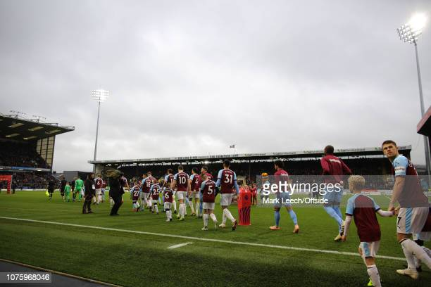 Burnley enter the field of play accompanied by mascots prior to the Premier League match between Burnley FC and West Ham United at Turf Moor on...