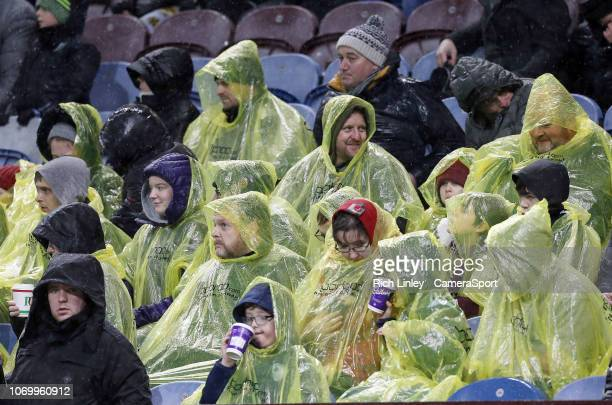 Burnley fans anxiously watch the second half action in soaking wet conditions during the Premier League match between Burnley FC and Brighton & Hove...