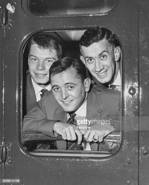 Burnley Football Club players Alexander Elder Brian Pilkington And Jimmie Adamson smiling from the door of their train carriage as they prepare to...