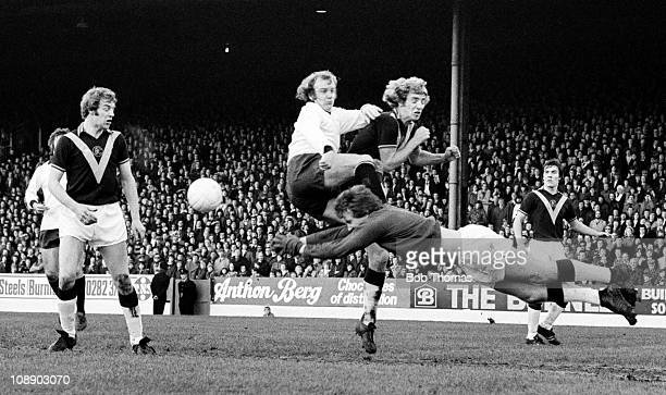 Burnley goalkeeper Alan Stevenson dives in bravely to punch the ball away from Derby County striker Francis Lee during their Division One match...