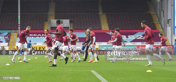 Burnley players warm up in front of the empty stand during the Premier League match between Burnley FC and Brighton Hove Albion at Turf Moor on July...