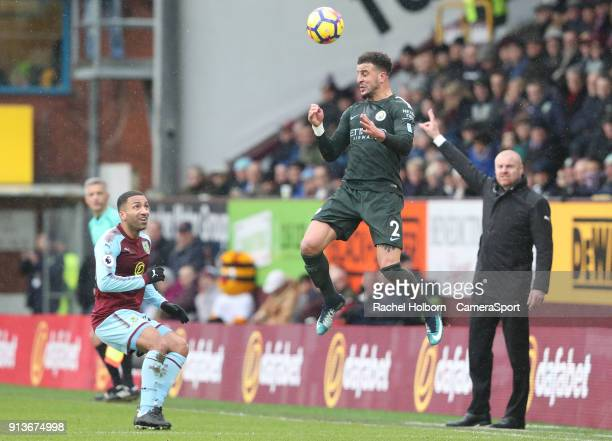 Burnleys Aaron Lennon and Sean Dyche look on as Manchester City's Kyle Walker heads the ball during the Premier League match between Burnley and...