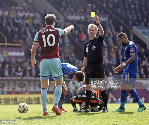 Burnley's Ashley Barnes is shown a yellow card by Referee Martin Atkinson for his challenge on Leicester City's Kasper Schmeichel during the Premier...