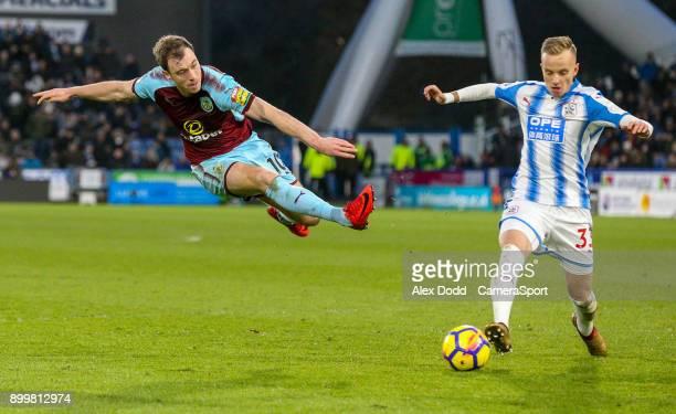 Burnley's Ashley Barnes shoots at goal under pressure from Huddersfield Town's Florent Hadergjonaj during the Premier League match between...