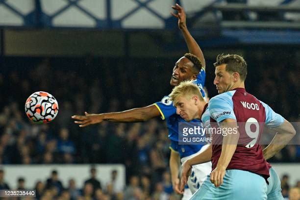 Burnley's English defender Ben Mee heads home the opening goal of during the English Premier League football match between Everton and Burnley at...