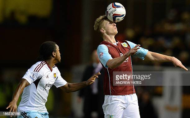 Burnley's English defender Ben Mee heads the ball as West Ham United's English defender Leo Chambers watches during the English League Cup fourth...