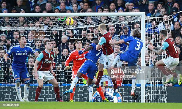 Burnley's English defender Ben Mee heads the ball to score his team's first goal during the English Premier League football match between Chelsea and...