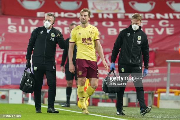 Burnley's English defender Charlie Taylor leaves the field with an injury during the English Premier League football match between Liverpool and...