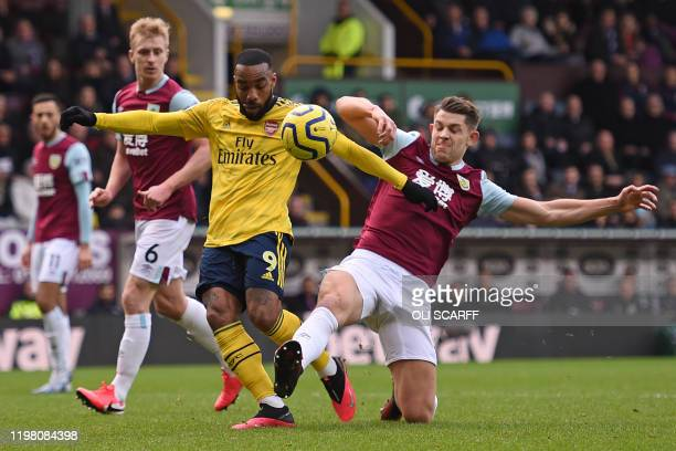Burnley's English defender James Tarkowski makes a tackle on Arsenal's French striker Alexandre Lacazette as he prepares to shoot during the English...