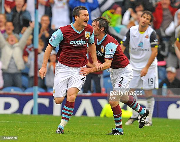 Burnley's English forward David Nugent celebrates with teammate Graham Alexander after scoring Burnley's third goal during the English Premier League...