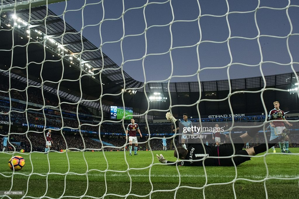 Burnley's English goalkeeper Tom Heaton dives but fails to save a shot from Manchester City's French defender Gael Clichy, resulting in City's first goal, during the English Premier League football match between Manchester City and Burnley at the Etihad Stadium in Manchester, north west England, on January 2, 2017. / AFP / Oli SCARFF / RESTRICTED TO EDITORIAL USE. No use with unauthorized audio, video, data, fixture lists, club/league logos or 'live' services. Online in-match use limited to 75 images, no video emulation. No use in betting, games or single club/league/player publications. /