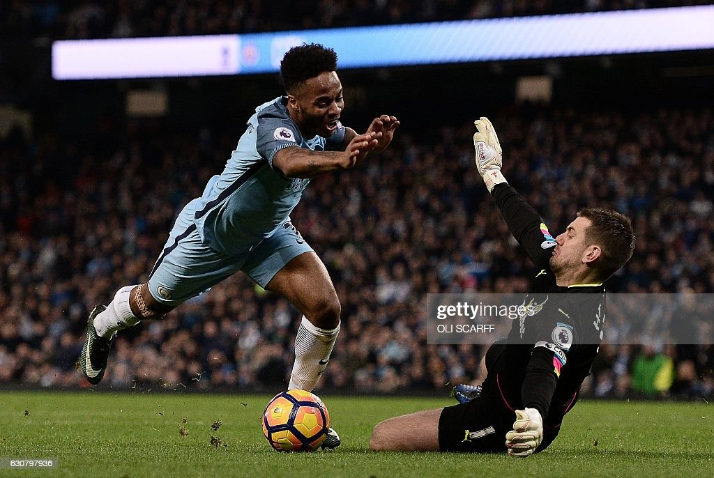 Burnley's English goalkeeper Tom Heaton (R) dives to save a shot from Manchester City's English midfielder Raheem Sterling during the English Premier League football match between Manchester City and Burnley at the Etihad Stadium in Manchester, north west England, on January 2, 2017. / AFP / Oli SCARFF / RESTRICTED TO EDITORIAL USE. No use with unauthorized audio, video, data, fixture lists, club/league logos or 'live' services. Online in-match use limited to 75 images, no video emulation. No use in betting, games or single club/league/player publications. /