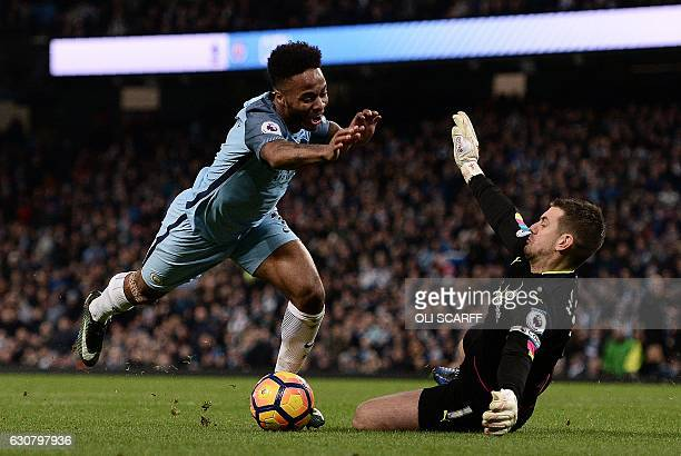 Burnley's English goalkeeper Tom Heaton dives to save a shot from Manchester City's English midfielder Raheem Sterling during the English Premier...