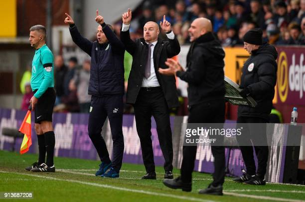 Burnley's English manager Sean Dyche Burnley's assistant manager Ian Woan and Manchester City's Spanish manager Pep Guardiola gesture on the...