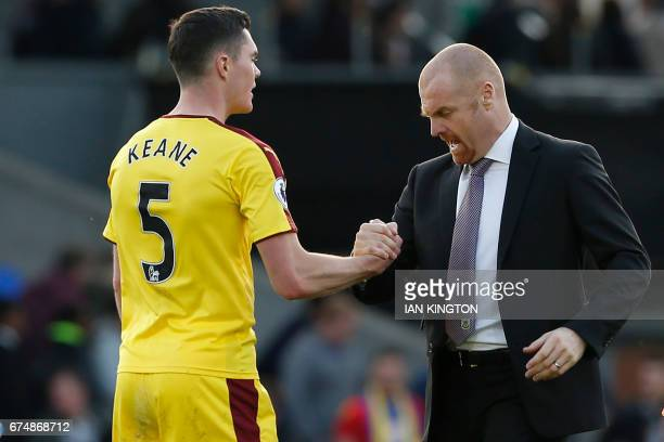Burnley's English manager Sean Dyche congratulates Burnley's English defender Michael Keane after the English Premier League football match between...