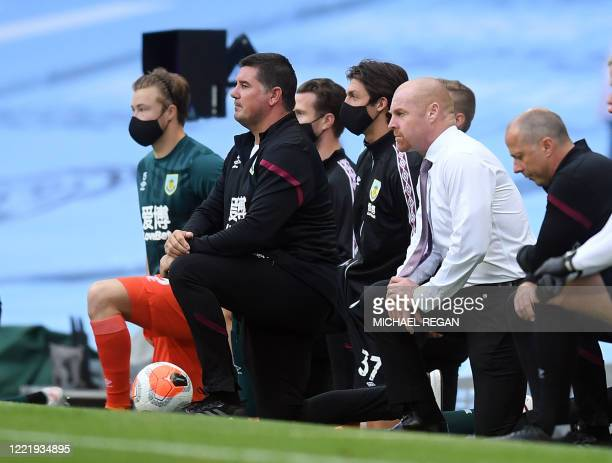 Burnley's English manager Sean Dyche takes a knee in support of the Black Lives Matter movement ahead of the English Premier League football match...