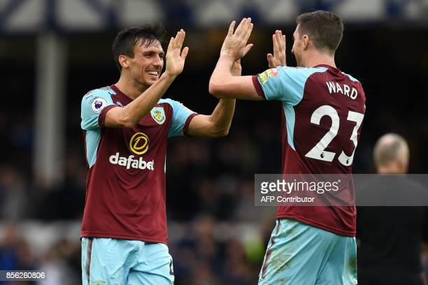 Burnley's English midfielder Jack Cork celebrates on the pitch with Burnley's Irish defender Stephen Ward after the English Premier League football...