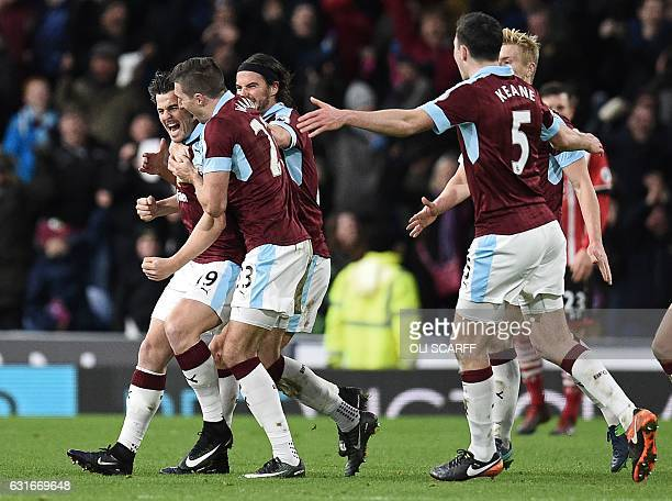 Burnley's English midfielder Joey Barton celebrates with teammates after scoring the opening goal of the English Premier League football match...