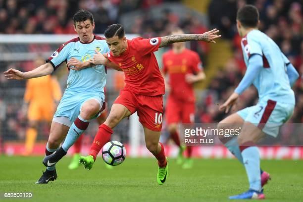 Burnley's English midfielder Joey Barton vies with Liverpool's Brazilian midfielder Philippe Coutinho during the English Premier League football...