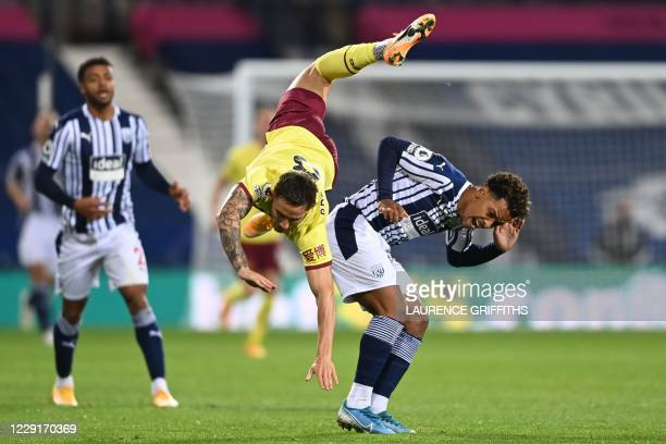 Burnley's English midfielder Josh Brownhill takes a tumble in a challenge with West Bromwich Albion's Brazilian midfielder Matheus Pereira during the...