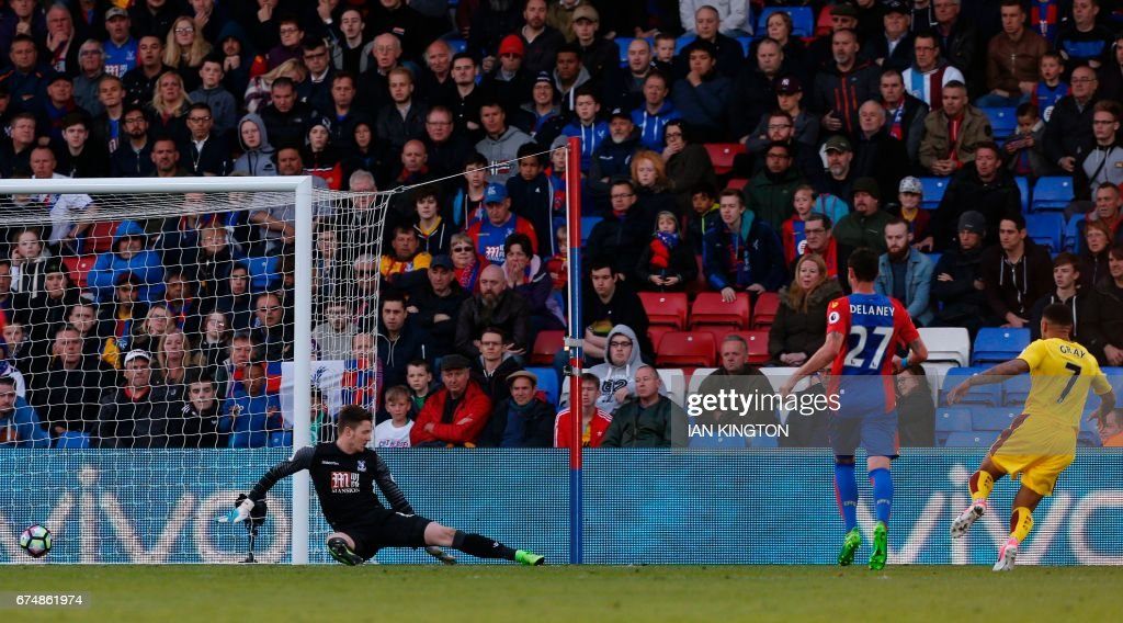 Burnley's English striker Andre Gray (R) scores their second goal past Crystal Palace's Welsh goalkeeper Wayne Hennessey (L) during the English Premier League football match between Crystal Palace and Burnley at Selhurst Park in south London on April 29, 2017. / AFP PHOTO / Ian KINGTON / RESTRICTED TO EDITORIAL USE. No use with unauthorized audio, video, data, fixture lists, club/league logos or 'live' services. Online in-match use limited to 75 images, no video emulation. No use in betting, games or single club/league/player publications. /