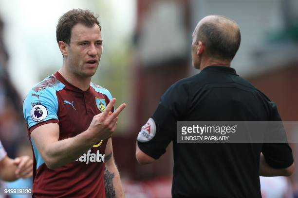 Burnley's English striker Ashley Barnes remonstrates with English referee Mike Dean after being shown a yellow card during the English Premier League...