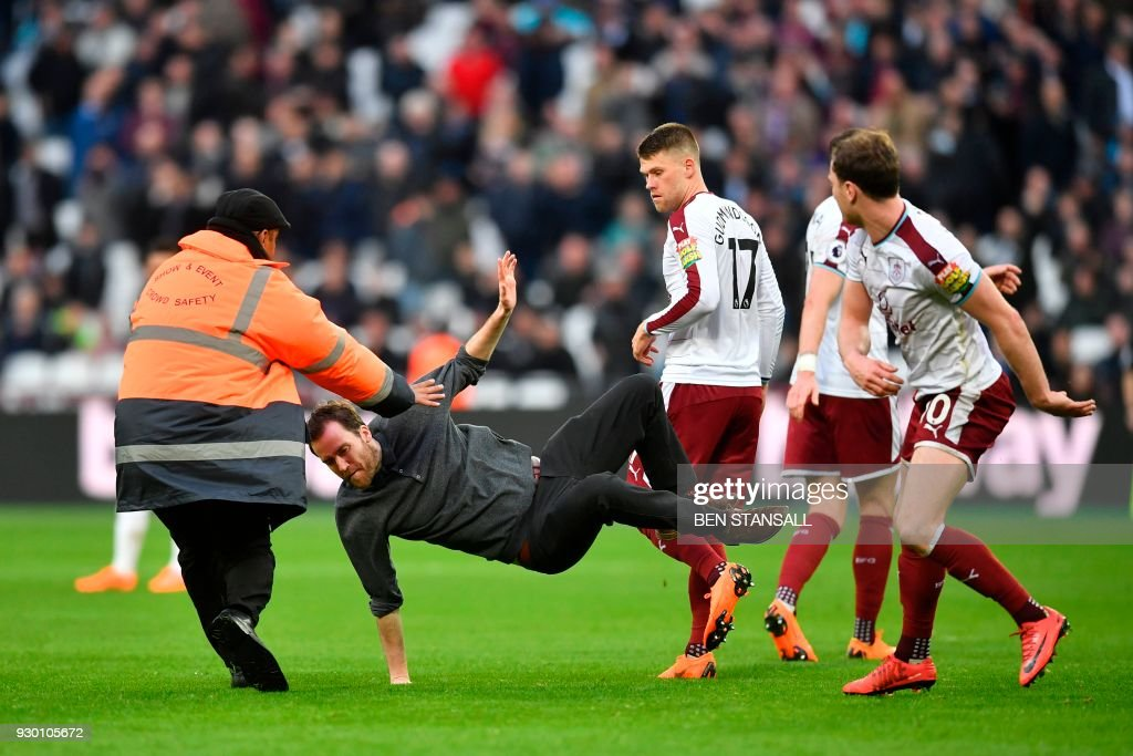 TOPSHOT - Burnley's English striker Ashley Barnes trips up a pitch invader during the English Premier League football match between West Ham United and Burnley at The London Stadium, in east London on March 10, 2018. / AFP PHOTO / Ben STANSALL / RESTRICTED TO EDITORIAL USE. No use with unauthorized audio, video, data, fixture lists, club/league logos or 'live' services. Online in-match use limited to 75 images, no video emulation. No use in betting, games or single club/league/player publications. /