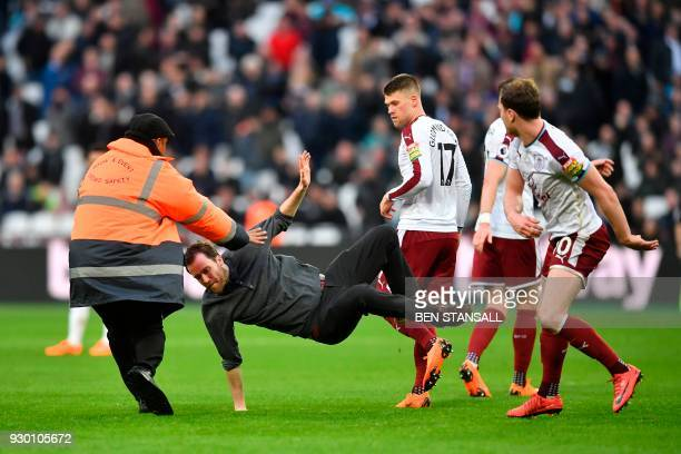 TOPSHOT Burnley's English striker Ashley Barnes trips up a pitch invader during the English Premier League football match between West Ham United and...