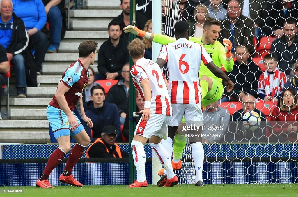 Burnley's English striker Ashley Barnes (L) watches his shot pass Stoke City's English goalkeeper Jack Butland (R) as he scores his team's first goal during the English Premier League football match between Stoke City and Burnley at the Bet365 Stadium in Stoke-on-Trent, central England on April 22, 2018. (Photo by Lindsey PARNABY / AFP) / RESTRICTED TO EDITORIAL USE. No use with unauthorized audio, video, data, fixture lists, club/league logos or 'live' services. Online in-match use limited to 75 images, no video emulation. No use in betting, games or single club/league/player publications. /