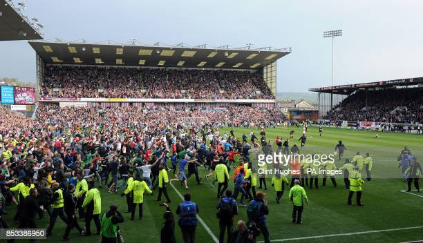 Burnley's fans celebrate by invading the pitch after their side win promotion to the Premier League during the Sky Bet Championship match at Turf...