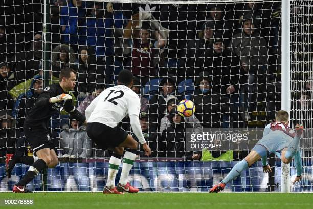 Burnley's Icelandic midfielder Johann Berg Gudmundsson heads past Liverpool's Belgian goalkeeper Simon Mignolet score their first goal during the...