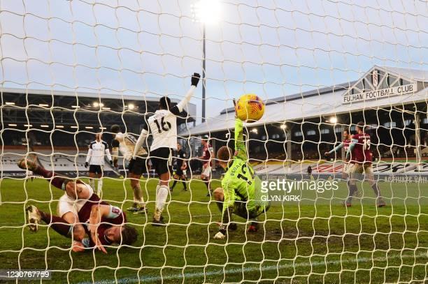 Burnley's Irish defender Kevin Long topples over after scoring his team's third goal past Fulham's Slovakian goalkeeper Marek Rodak during the...