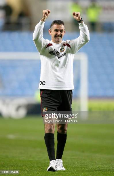 Burnley's Manager Owen Coyle celebrates with the traveling fans after victory over Coventry City