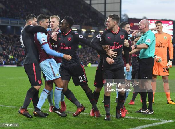Burnley's Matt Lowton is held back by Arsenal's Sead Kolasinac and Danny Welbeck after calshing with Aaron Ramsey during the Premier League match...