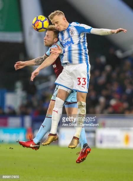 Burnley's Scott Arfield battles with Huddersfield Town's Florent Hadergjonaj during the Premier League match between Huddersfield Town and Burnley at...