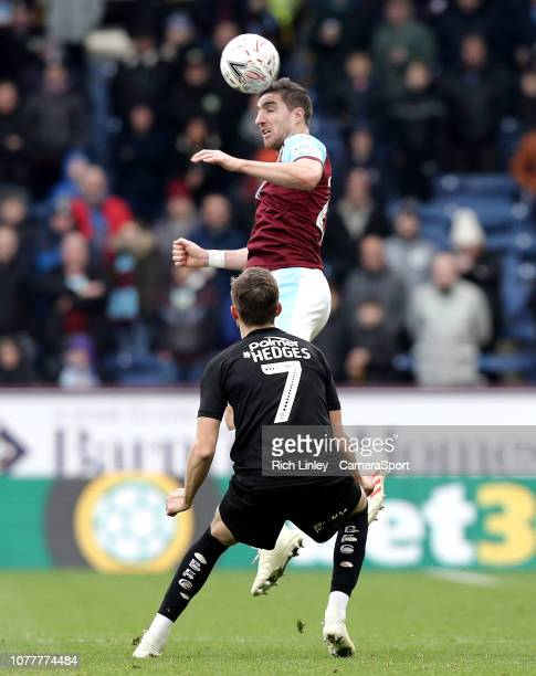 Burnley's Stephen Ward wins an aerial ball despite the attentions of Barnsley's Ryan Hedges during the FA Cup Third Round match between Burnley and...