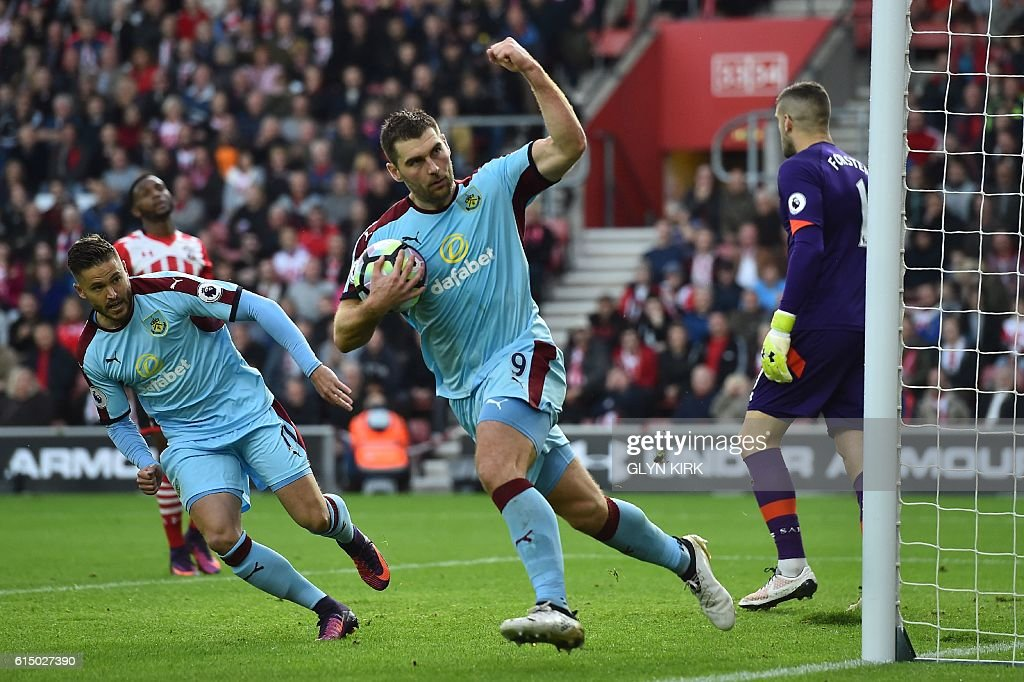 Burnley's Welsh striker Sam Vokes (C) celebrates after scoring from the penalty spot during the English Premier League football match between Southampton and Burnley at St Mary's Stadium in Southampton, southern England on October 16, 2016. / AFP / GLYN KIRK / RESTRICTED TO EDITORIAL USE. No use with unauthorized audio, video, data, fixture lists, club/league logos or 'live' services. Online in-match use limited to 75 images, no video emulation. No use in betting, games or single club/league/player publications. /