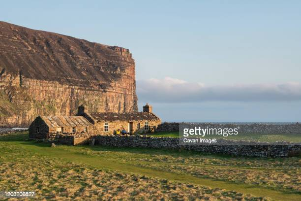 burnmouth bothy stone shelter in below dramatic sea cliffs at rackwick bay, hoy, orkney, scotland - island stock pictures, royalty-free photos & images